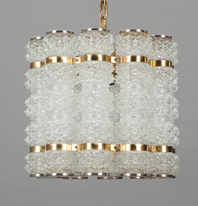 A Pendant by Konst Hant Verk Tyringe, Sweden. Circa 1960th-70s. Glass probably by Orrefors. Cut glass , polished nickel and brass.  Glass H-9