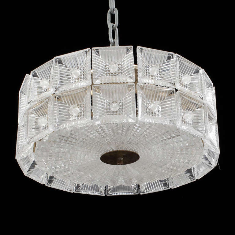 A pendant by Carl Fagerlund for Orrefors. Clear textured glass with brass hardware. Existing European wiring, rewiring available upon request. Two fixtures available. Pricing for each. Two available.