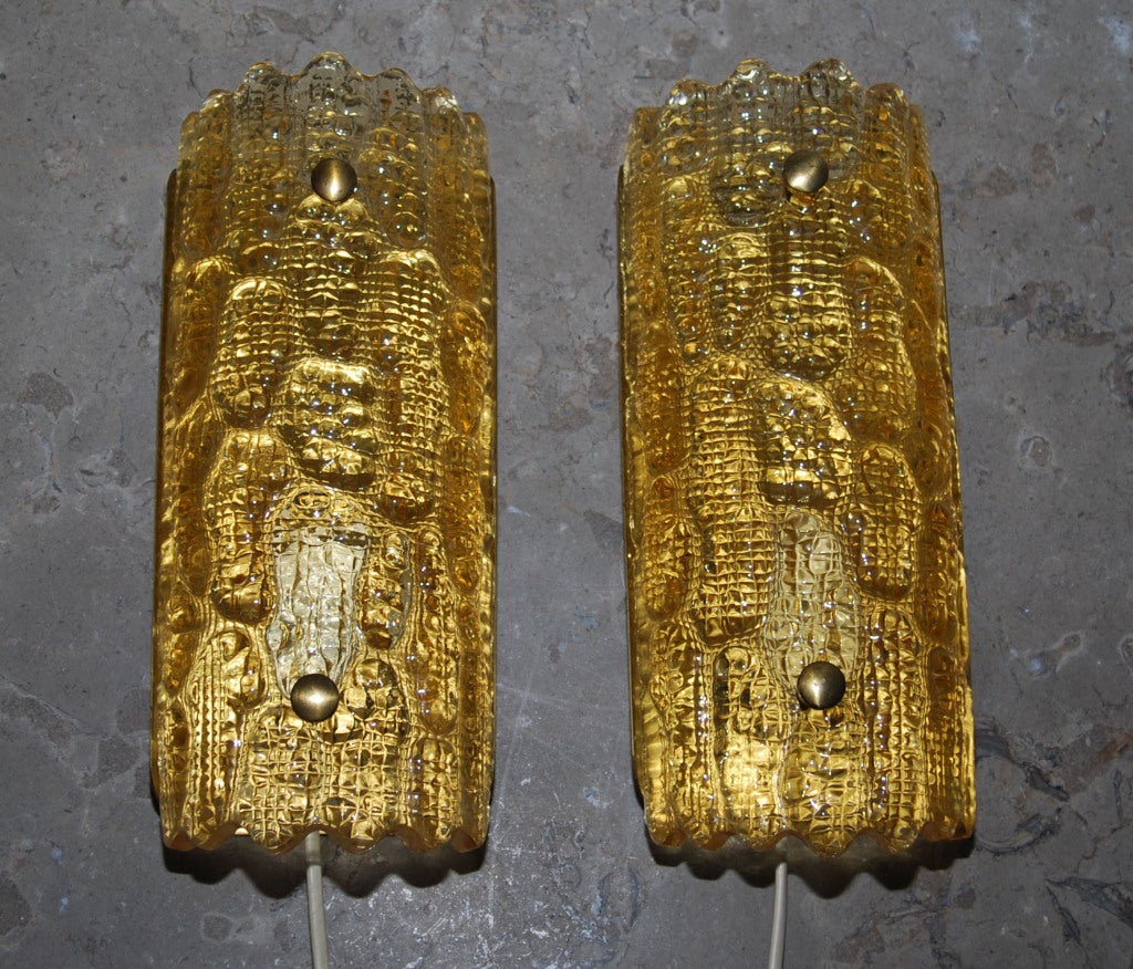 A pair of wall lights by Carl Fagerlund. Orrefors amber colored crystal glass, produced by Lyfa. Existing European wiring. Re-wiring available upon request.