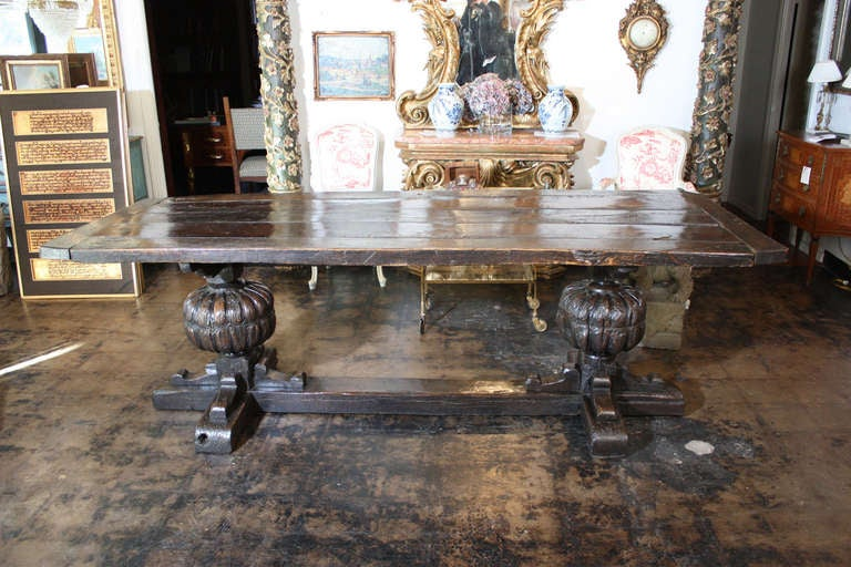 An Antique Oak and Elm wood console with massive hand carved buns supporting thick plank top with consistent gorgeous patina circa late seventeenth century. See additional photos on dealers website.