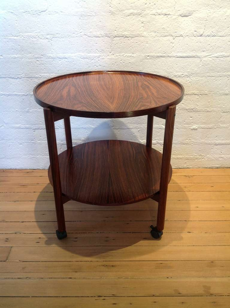 A rosewood danish bar cart with a stunning dark rich color. The top lift off to use as a serving tray.  On wheels for easy moving.