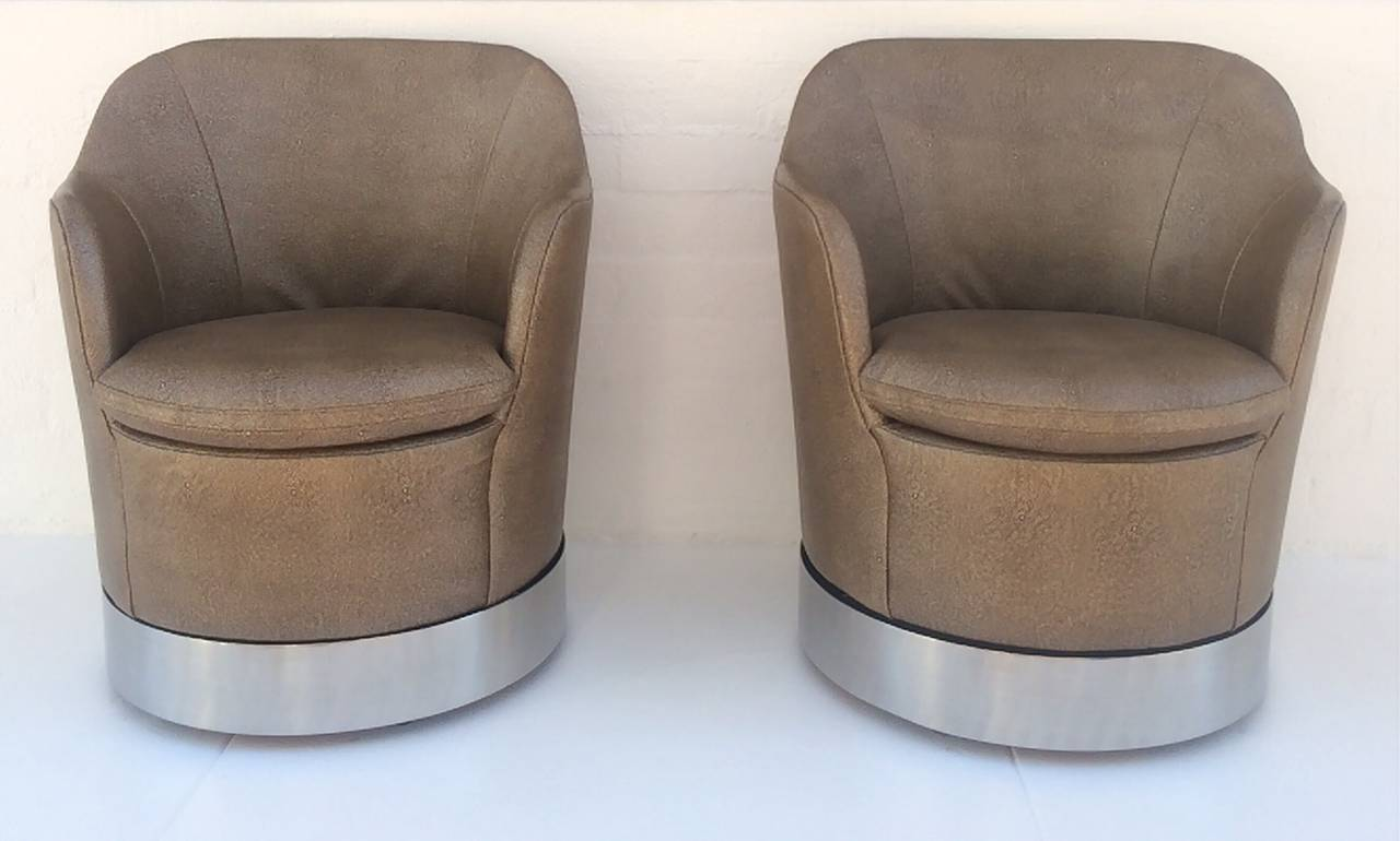 A pair of swivel lounge chairs by Phillip Enfield.  Stainless steel base with newly reupholstered Shagreen leather.  These gorgeous chairs swivel 360°, circa 1960s