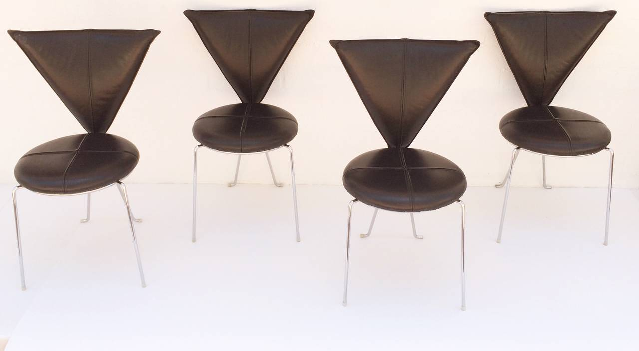 A rare set of four black leather dining chairs with chrome legs. Made in Germany, circa 1980s. Designed by Helmut Lubke & Co. with a triangle shaped back and a round seat these chairs have a Memphis look to them. Both the back and the seat have