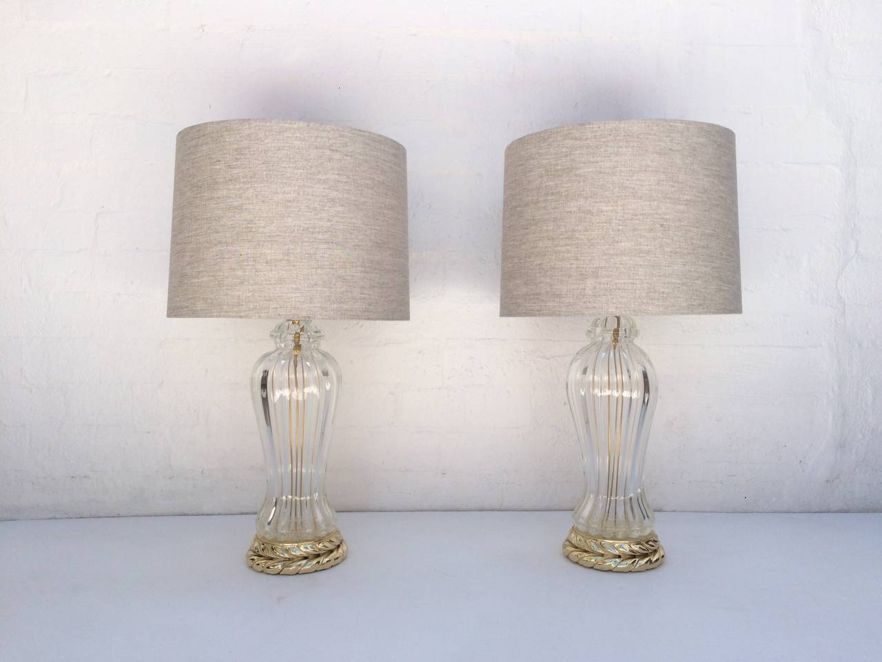 Pair of Italian Murano glass table lamps with newly re-plated polished brass bases.  Newly rewired with new polished brass hardware.  New oatmeal linen shades.  Made by The Marbro Lamp Company, circa 1960s.