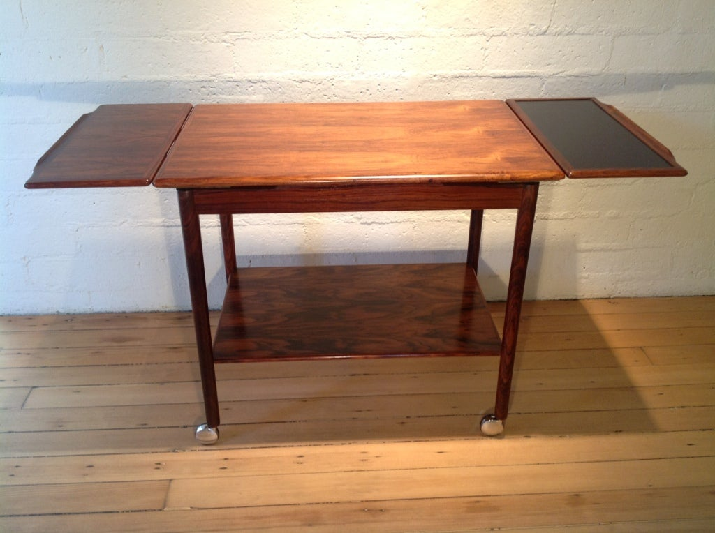 A rosewood bar cart with pullout sides that makes into a larger top. one pullout is all rosewood,the other has a black type of resin for setting ice bucket or drinks as to not stain the rosewood. Was made by Drylund in Denmark.  With pullouts