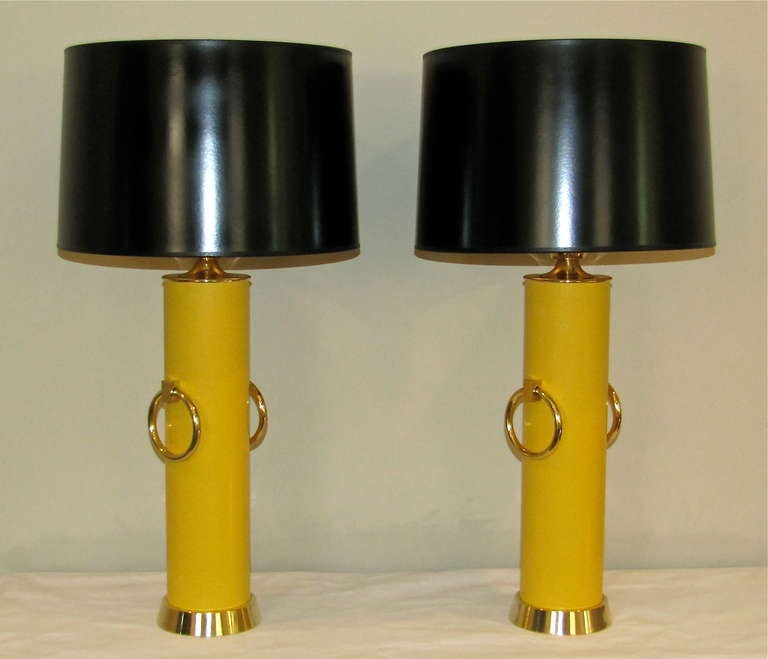Pair of distinctive table lamps designed by Tommi Parzinger for Lightolier. Overscale brass rings and brass hardware with original glass diffusers each signed LIGHTOLIER on the rim and restored marigold yellow lacquer body. These lamps were designed