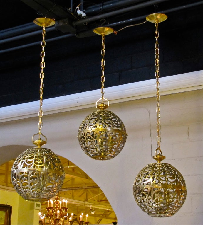 Trio of high quality Asian pierced brass pendants newly wired with new triple cluster light sockets and solid brass fittings. Includes chain and ceiling cap, ceiling drop can be adjusted as needed. All 3 Pendants 11.5