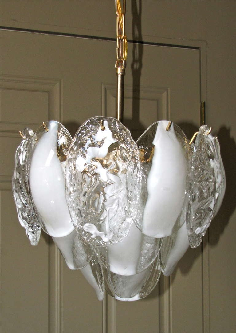 Italian chandelier by Mazzega composed of two alternating styles of clear and white handblown glass panels suspended on custom brass frame. Newly wired. Total height to ceiling cap 33