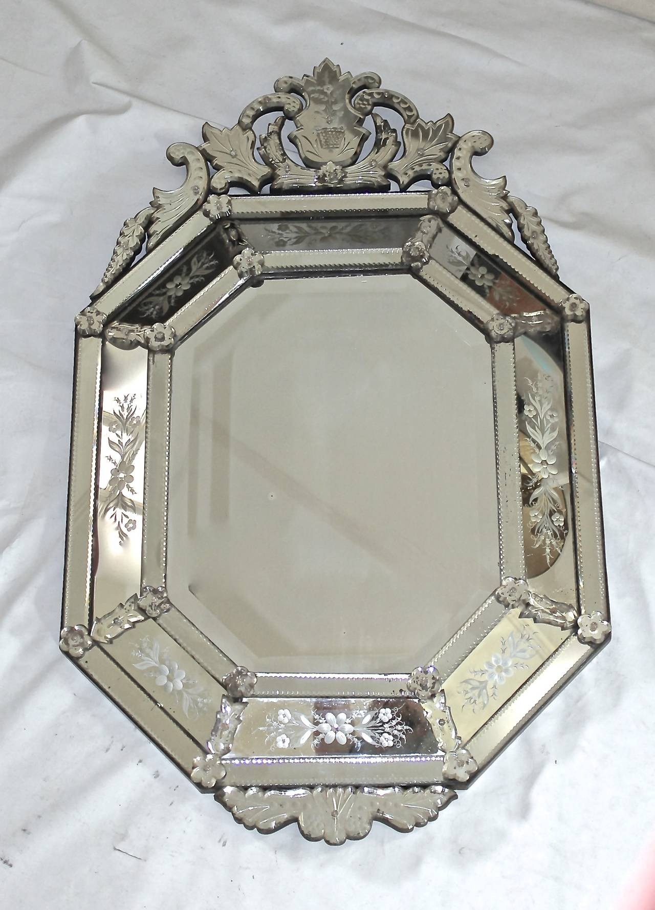 Exquisite octagonal Venetian Italian 1920s beveled mirror surrounded with intricately etched floral and leaf motif panels.  This item is located at our Dallas showroom.