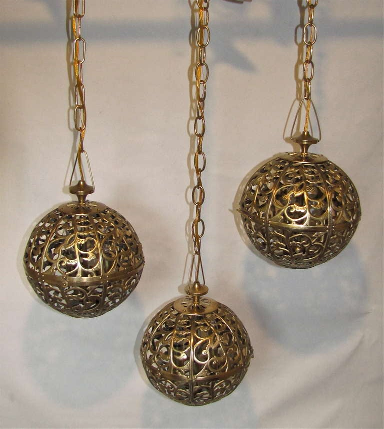 Trio of high quality Asian pierced brass pendants newly wired with new triple cluster light sockets and solid brass fittings. Includes chain and ceiling cap, ceiling drop can be adjusted as needed. All 3 Pendants 9