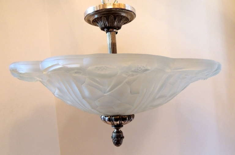 A wonderful French Art Deco silvered bronze and art glass flush mount fixture set with four lights inside.