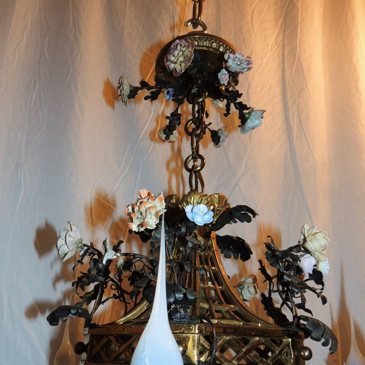 This very delicately detailed porcelain flower French bronze lantern has four arms and a light in the lantern. Each of the scroll decorated arms frame the beautiful lantern which has the original textured glass which is on the four panels. The