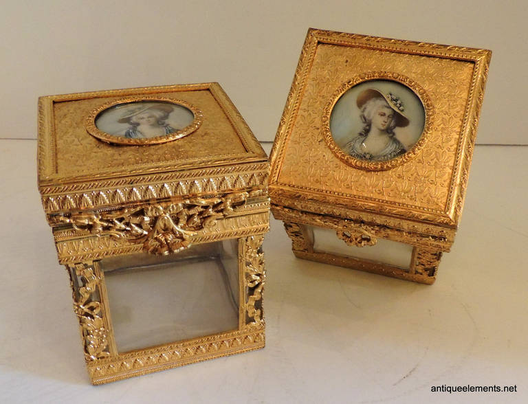 This elegant pair of bronze boxes are decorated with miniature portraits of two elegant ladies and have crystal inserts and mirrors on the box interiors. One of the boxes has a mirror that is stained, the other is in good condition. A beautiful