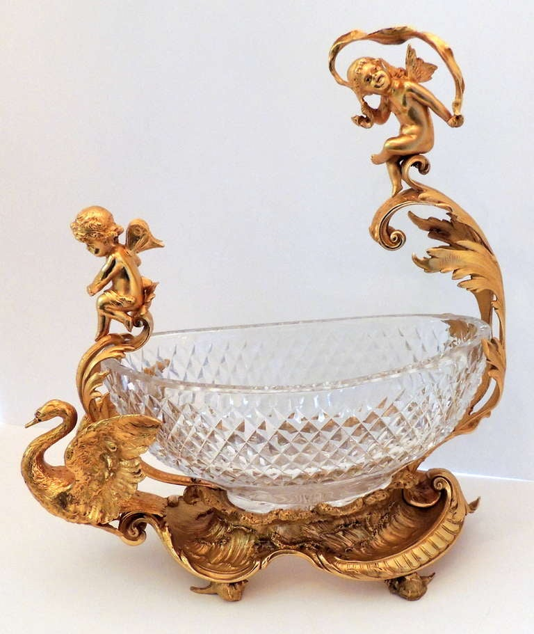 Exceptional French figural doré bronze and cut crystal centerpiece, featuring two mounted cherubs and a swan.