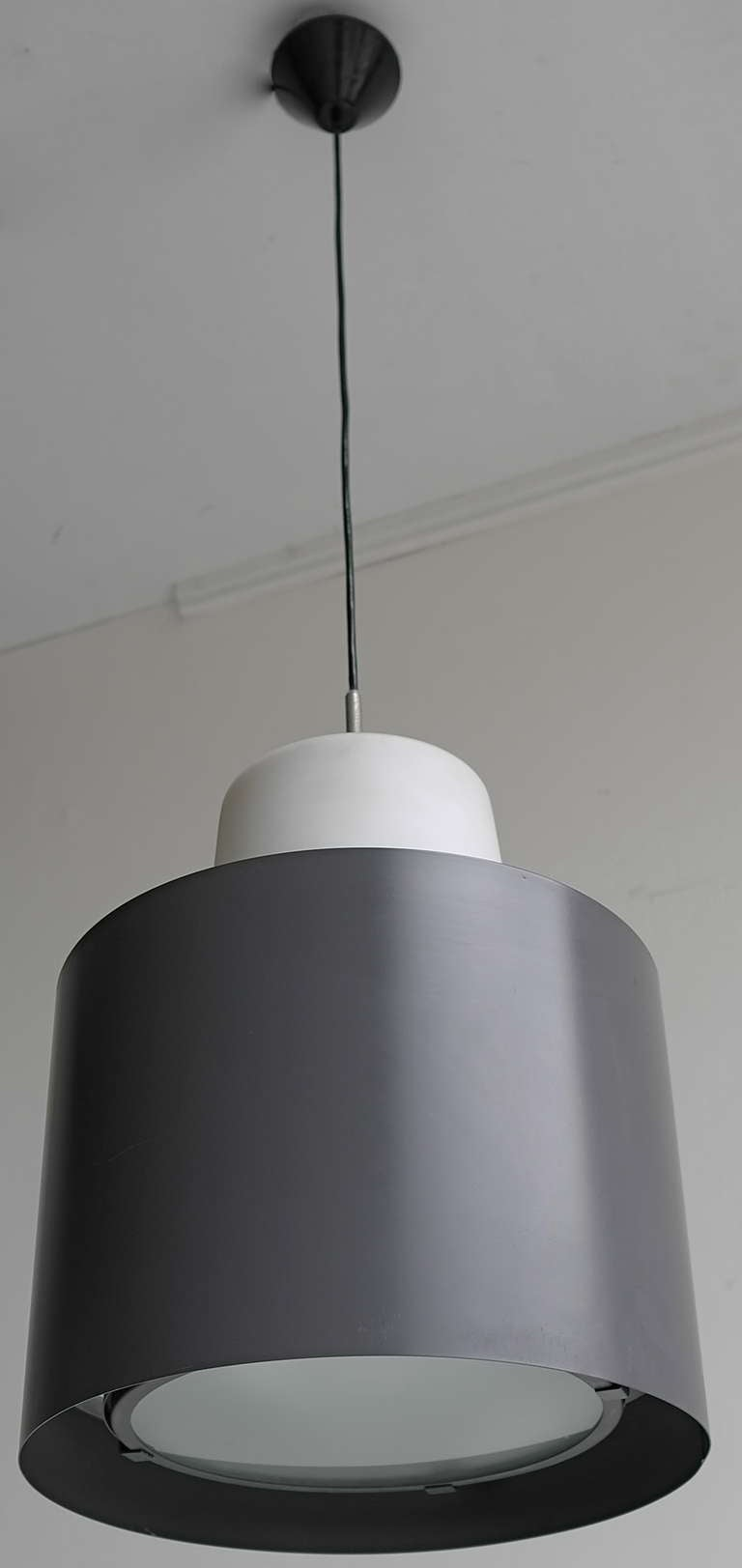 Three large Industrial metal and opaline glass pendant lights, 1960s. These lamps can be adjusted in height.