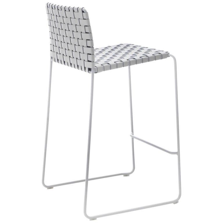 Italian modern bar or counter stool with the highest quality leather worked into a woven design and painted legs. Chrome or painted steel frame finished aluminium, matt white, bronze, matt black or raw natural, in round section, with seat and back