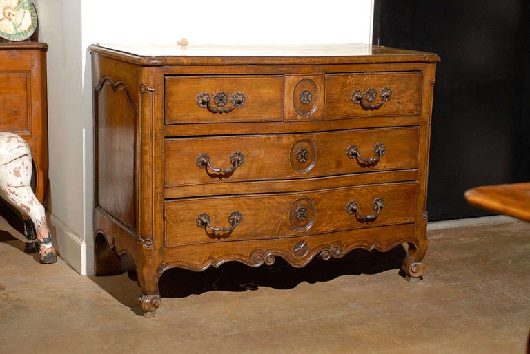 A French Louis XV period walnut four-drawer serpentine commode from the 18th century, with scalloped skirt and star motif. Born in France during the reign of king Louis XV, this exquisite walnut commode features a rectangular planked top with