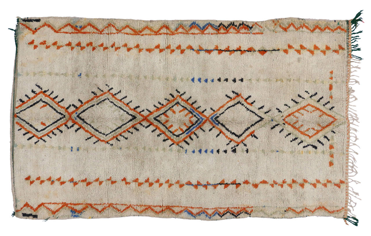 This eclectic vintage Moroccan Azilal rug features a stacked diamond protection design along the center with colors of orange, black, blue and a muted mint green on a creamy beige field. Azilal rugs with their plush pile and sturdy weave make them