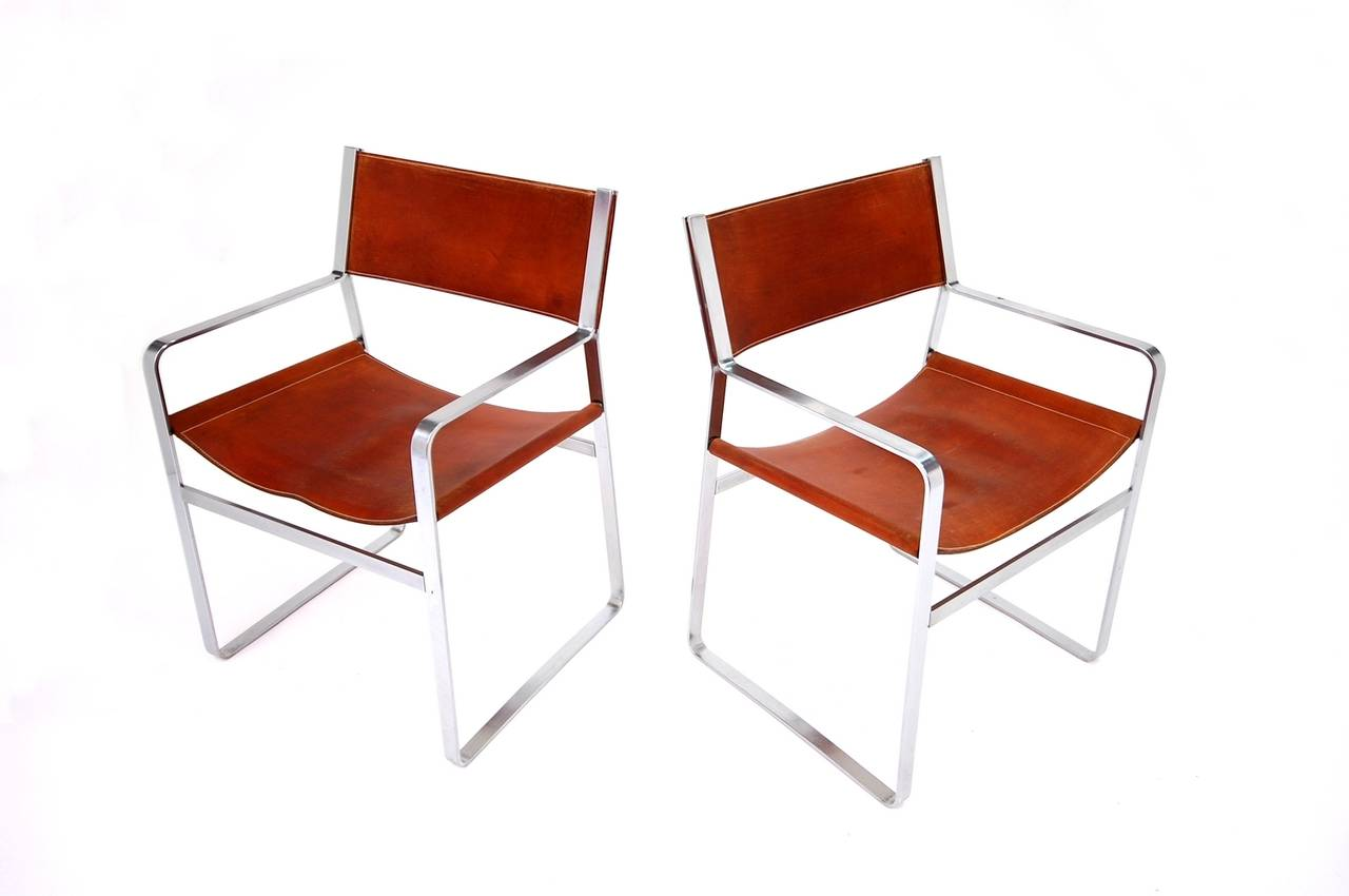Rare pair of JH-813 armchairs by Hans J. Wegner with frames of flat steel and original handstitched saddle leather.   Sketched in wood by Wegner in 1947 for the Copenhagen cabinet maker's guild exhibition, but not actually manufactured until the