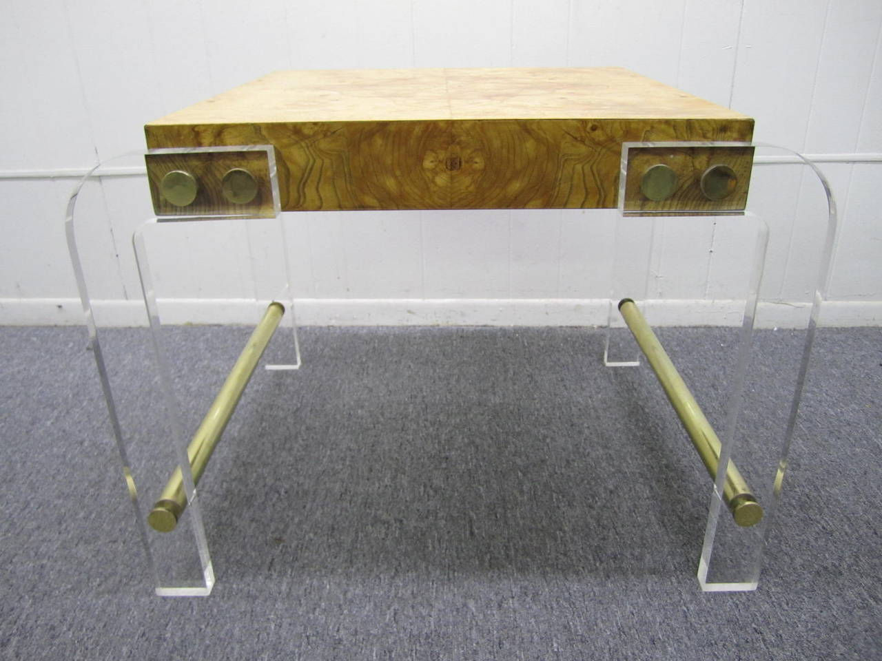 Simple, iconic Milo Baughman style side table. Arched Lucite legs are attached to the double book matched olive ash burl slab top with polished brass disks. Brass stretchers at base.