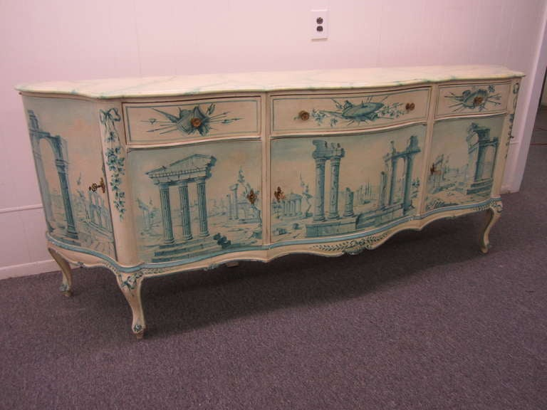 Wonderful early 20th century french painted credenza buffet. Wow! is all i can say about this amazing hand-painted masterpiece. This credenza has wonderful hand-painted details inside and out. The doors are painted on both sides with ancient ruins
