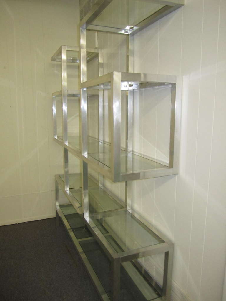 Fabulous large scale chunky aluminum and glass etagere.  You will love the mellow patina the thick aluminum frame has acquired. Fill this with all your wonderful treasures you have collected or even stack some art books on the generous sized shelves.