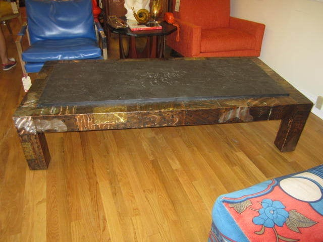 Very handsome Paul Evans patchwork metal coffee table. The top has a textured piece of heavy slate in wonderful vintage condition. The base is a variety of metals patchworked together to create an amazing mosaic of color and texture. This table will