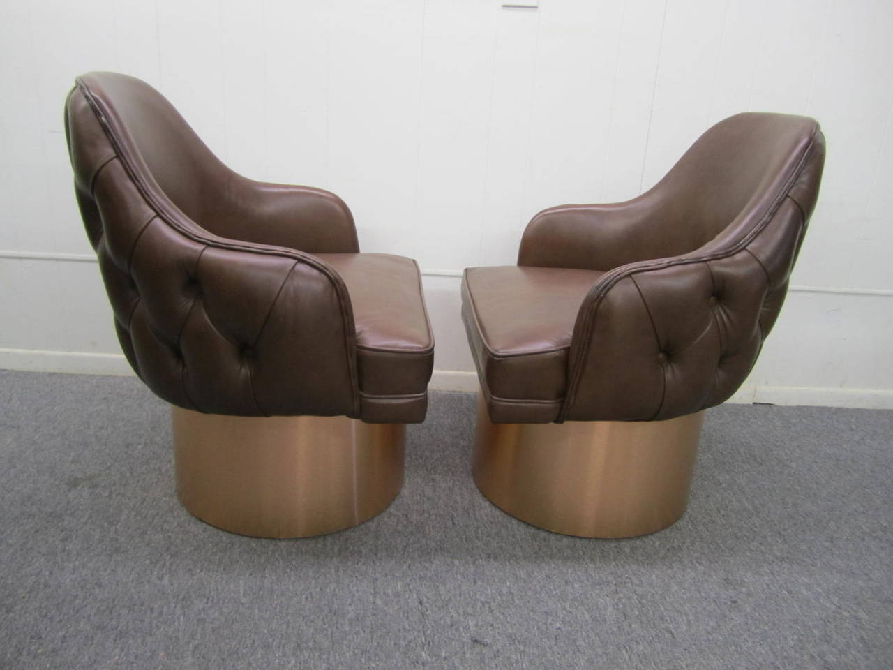 Excellent set of four Milo Baughman style leather tufted swivel chairs. This set retains their original chocolate brown leather in nice vintage condition with only minor signs of wear. The tall brushed copper metal bases look amazing and swivel