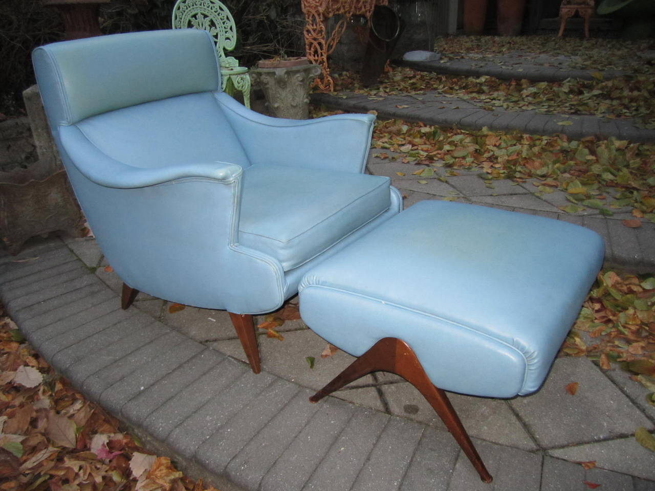 Exciting Mid-Century Modern lounge chair with matching ottoman. Wonderful swooping arms with a comfortable seat and back that leans back slightly. The ottoman actually makes the chair with its sculptural Space Age splayed walnut legs. Upholstered in