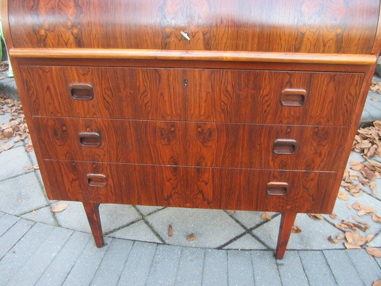 GORGEOUS DANISH MODERN ROSEWOOD ROLL TOP DESK.  THE ROSEWOOD IS VERY FIGUERED AND HAS A RICH DEEP COLOR.  I LOVE THE BOOKMATCHED GRAINING ON THE WHOLE FRONT-VERY EXOTIC.  THE DRAWERS ARE SOLID WOOD SECONDARY WOODS AND ALL THE DRAWERS ARE WELL