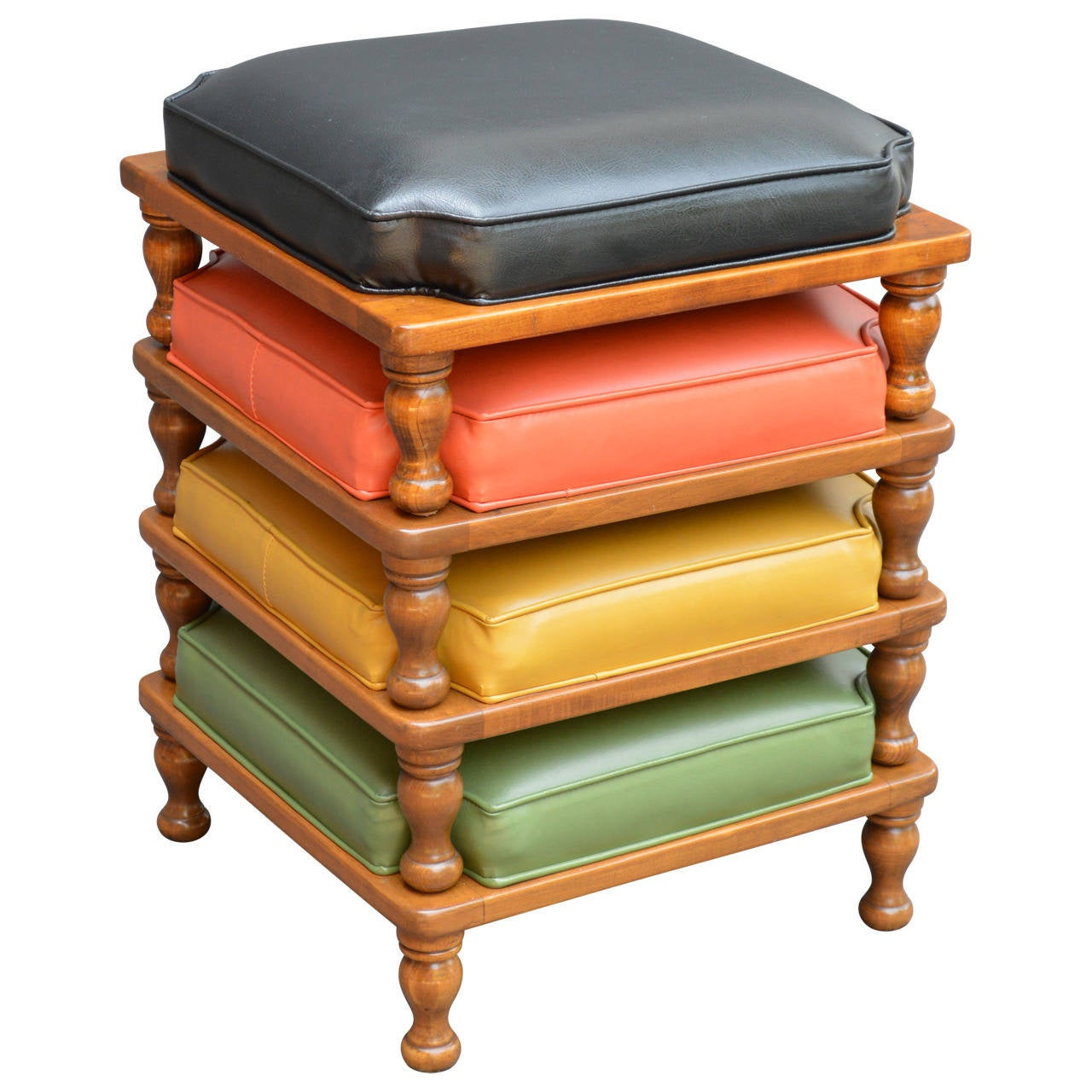 Cool set of four Ethan Allen stacking ottomans from the 1970s! The original Naugahyde cushions are very versatile in black, orange, yellow and green and sit atop a medium wood finish. Labeled Ethan Allen American traditional.
