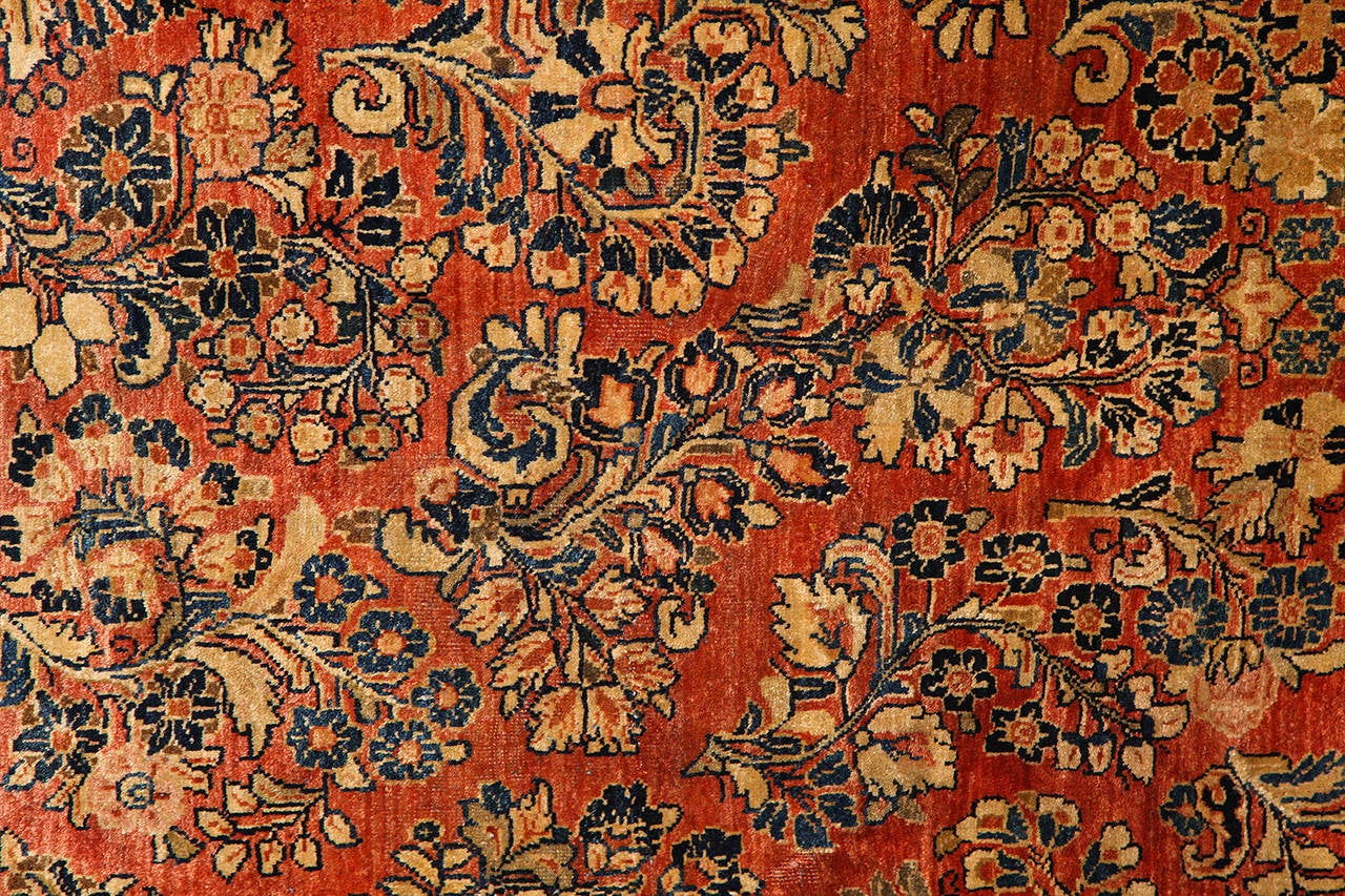 This Persian Sarouk carpet created, circa 1910 consists of a pure wool hand-knotted pile, cotton warp and thread and natural vegetable dyes. Unlike many other existing Sarouks from this time period, the deep reds, golds, blues and blacks of this