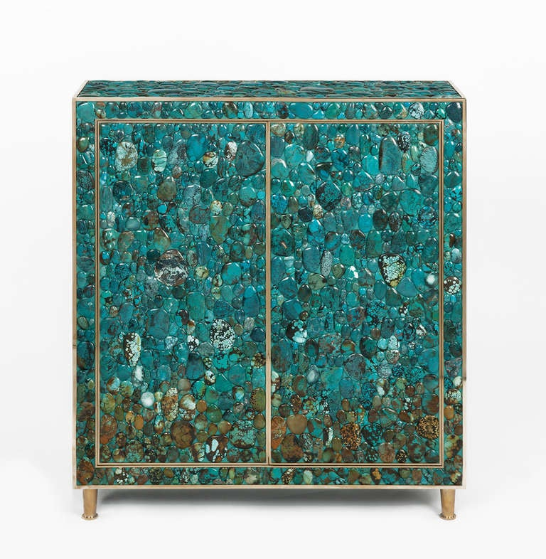 Cabinet in natural wood covered with turquoise cabochons, frame and feet in brass. Two doors in front. Two shelves inside.  Lead time: 7-8 weeks.