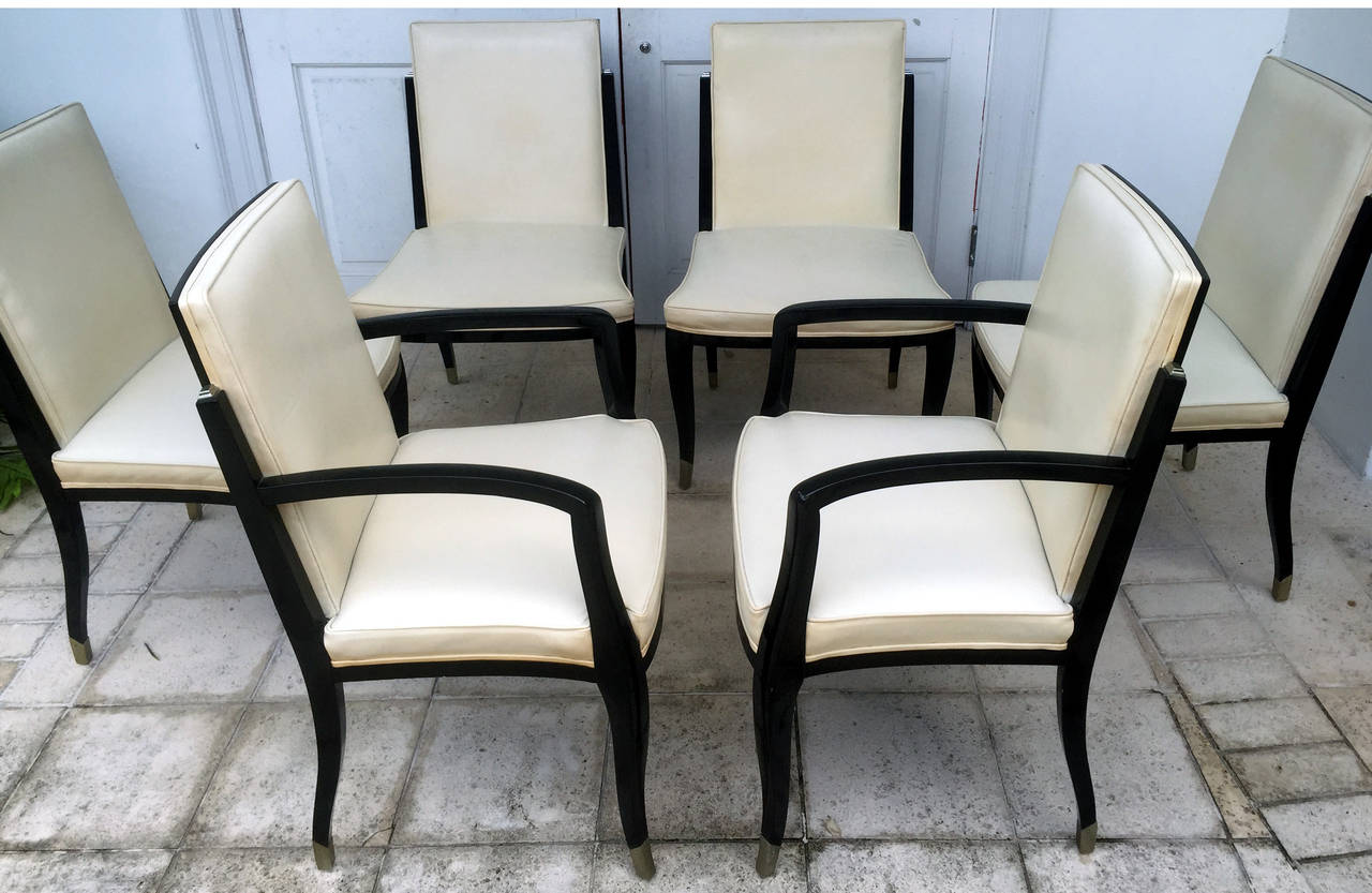 A custom-made set of six dining chairs in the style of Art Deco consisting of two arm and six side. Black lacquer with off white leather upholstery, these chairs display elegant form with slightly curvy arms and back legs, high quality construction
