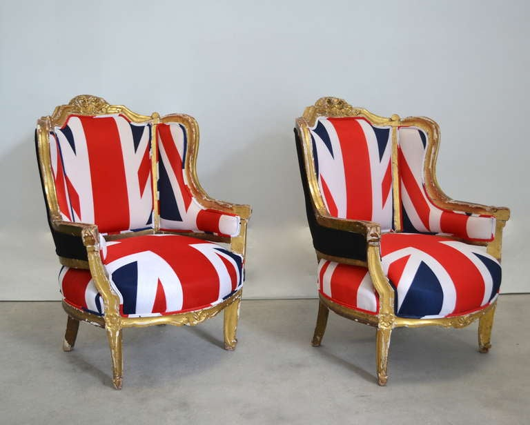 Whimsical pair of Louis XV style water gilt wing back bergeres upholstered in Union Jack flags, c. late 19th century.