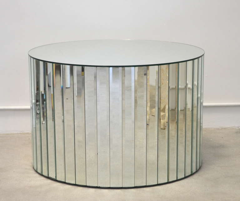 Glamorous beveled mirror occasional table of drum form, c. 1950s -1960s. This exquisite Hollywood Regency cocktail table, coffee table or side table is designed with a beveled mirror top supported by a base of interlacing concentric beveled strips