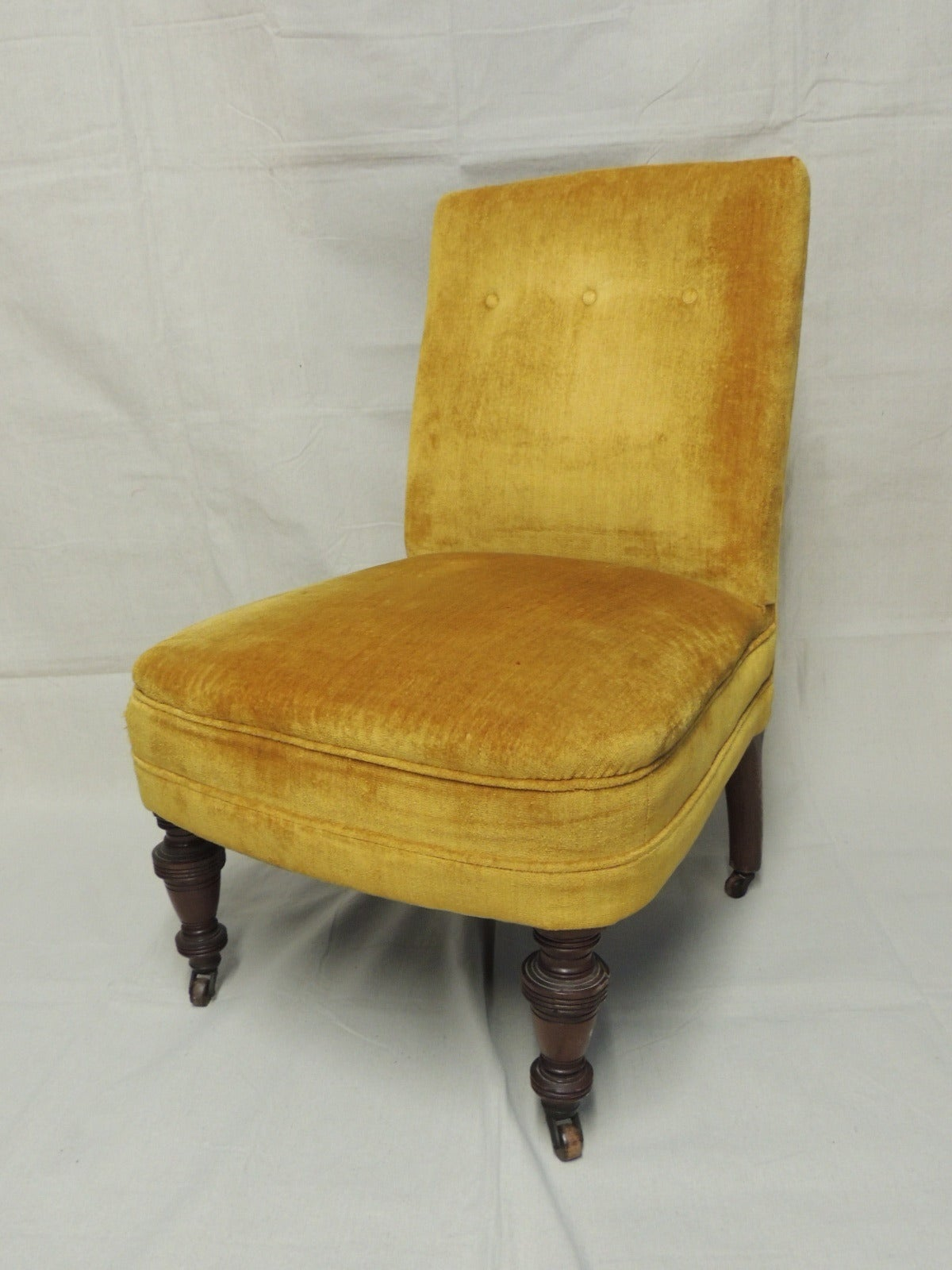 English slipper chair with turned wood legs and casters on all-four legs, tufted back. Upholstered in original silk yellow silk velvet, The velvet has a few stains and a small tear. Great old-world look as-is, but the frame is strong and the lines