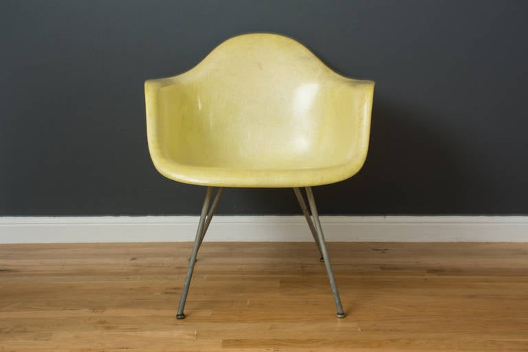 This is a Mid-Century Modern 'lemon yellow' zenith rope edge, LAX fiberglass shell chair designed by Charles and Ray Eames for Herman Miller in the 1950's. It has the 'x' base, original glides, and early Herman Miller/Zenith label.