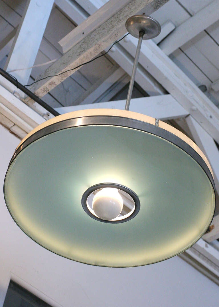 This streamlined aluminum ceiling lamp features an original frosted glass shade embellished with a polished aluminum neck. The piece hangs at 34 inches and can be shortened to desired height. We have several available.   The fixture originally made