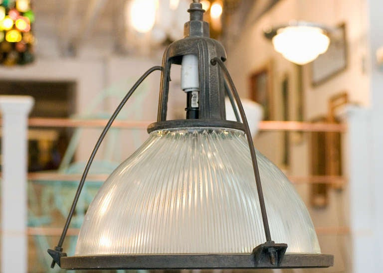 This industrial yet elegant hanging lamp from the 1940s features a Holophane glass shade. The pendant is connected by an aluminum casing fixed to the top of the light fixture.  Please inquire us if you would like a different quantity of lights.