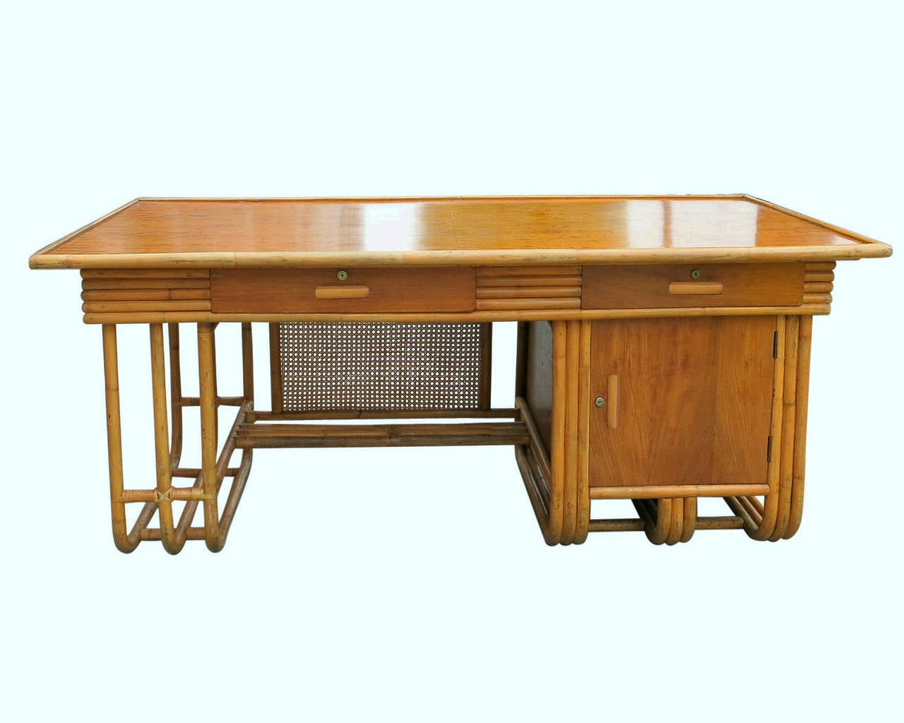 A large Jean Royère style streamline rattan executive desk with Filipino mahogany finished sections: Drawer fronts, side panels and top. Also has an optional glass top. The desk features two center pull drawers and a side cabinet with locks on
