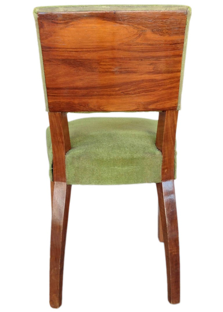 Set of four French Art Deco walnut dining chairs with large decorative wood backboard and dark green coverings,   France, circa 1920.