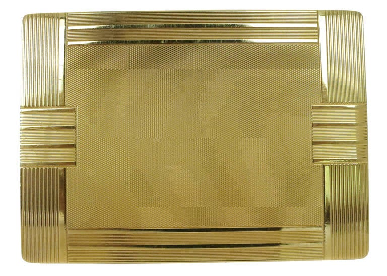 A solid 18-carat gold case with geometric Art Deco lines, this cigarette case has lines textured along the exterior and is completed with a complex grid pattern in the center.  It also comes with its original slip pouch.
