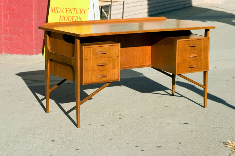 Large Danish teak desk in the style of Kai Kristiansen with floating drawers and table top. The desk features six side drawers, a curved front lip and a 50