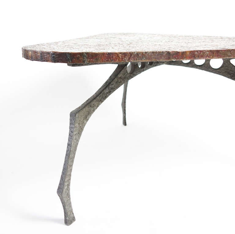 A stunning biomorphic center table. Like much of the best studio furniture of designers like Paul Evans, this marvelous piece has the elemental presence of modern sculpture. From afar the hammered copper top is like a placid seascape, up close it