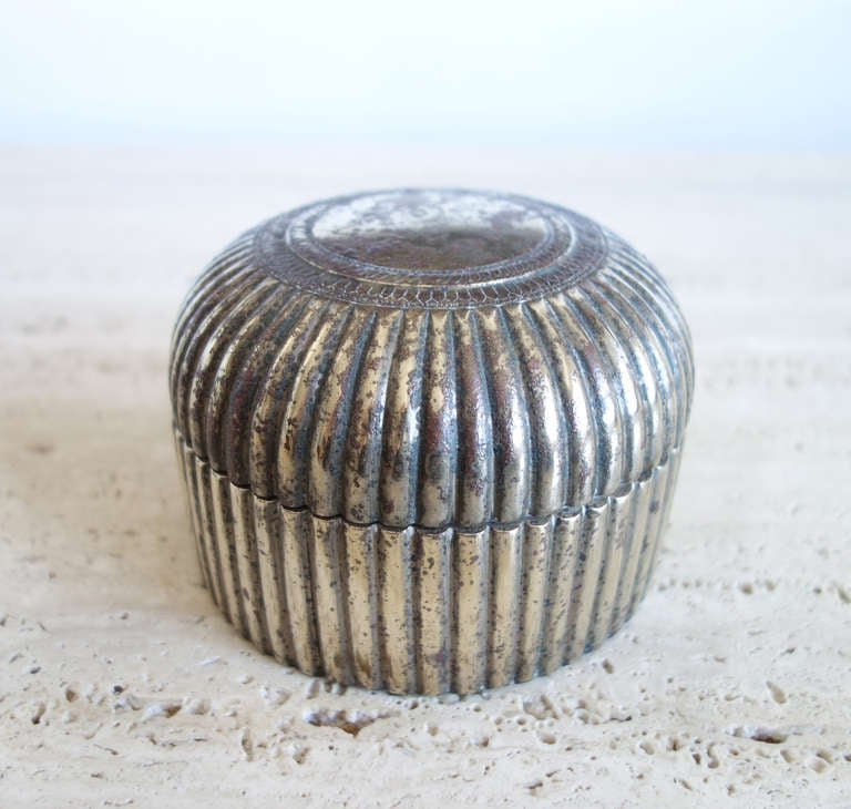 This North Indian pandan box would have been used to store pandan leaves. The leaves were wrapped around a mixture of lime paste, grated areca nut and flavorings to form a small parcel which would then be chewed. To our eyes, the rough patina and