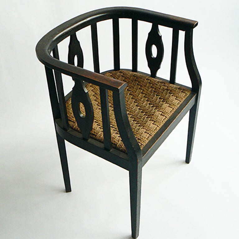 The restrained elegance of the design is typical of early 20th century Austria. Note the Vienna Secession influence in the verticality of the barrel-back, the alternating pierced and plain splats, the contrast of the ebonized wood with the supple