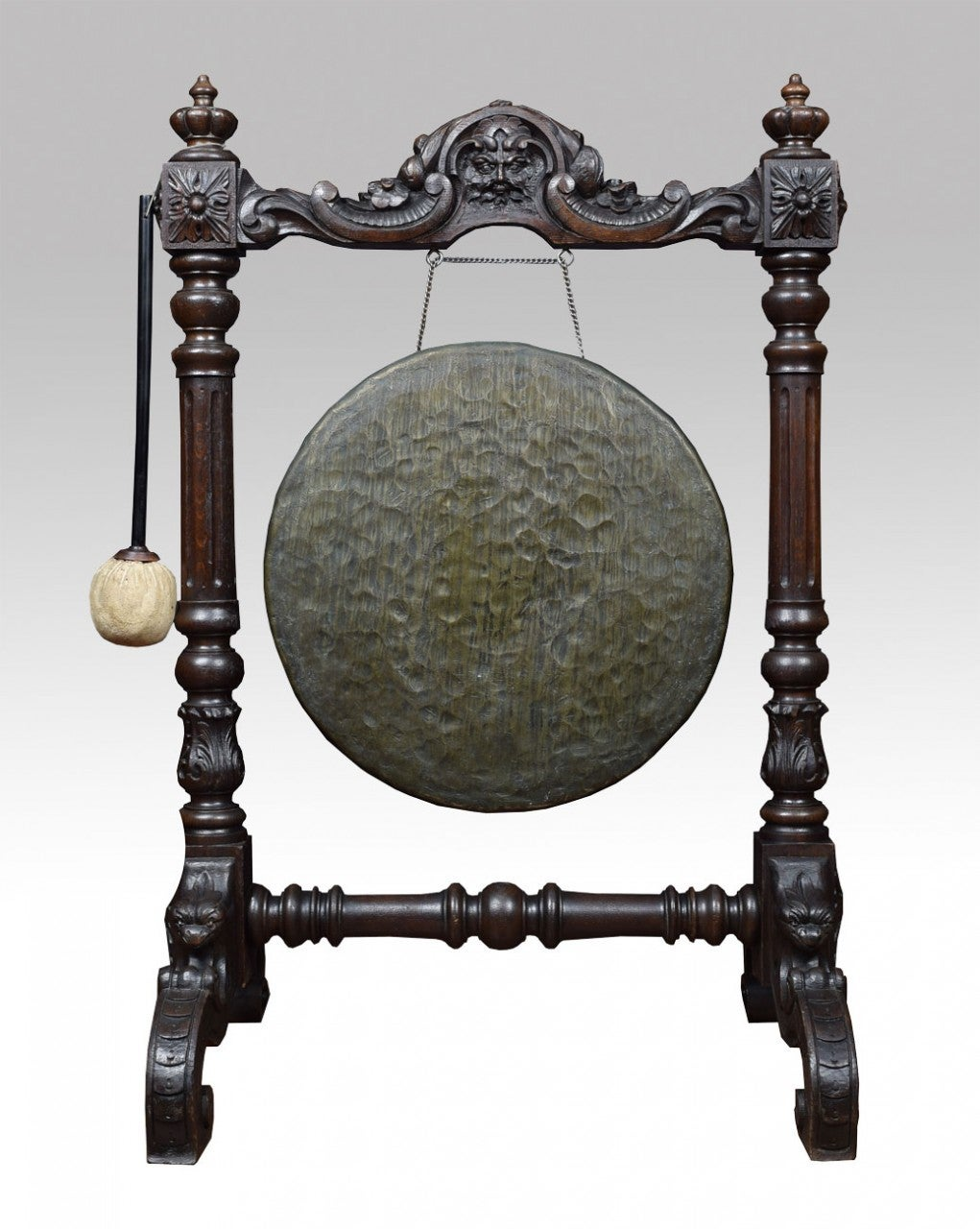 Large Carved Victorian oak dinner gong, the frame with mask, scroll and leaf carved crest flanked by mask carved, fluted uprights raised up on carved trestle base, with original striker Dimensions Height 40 Inches Width 25.5 Inches Depth 21