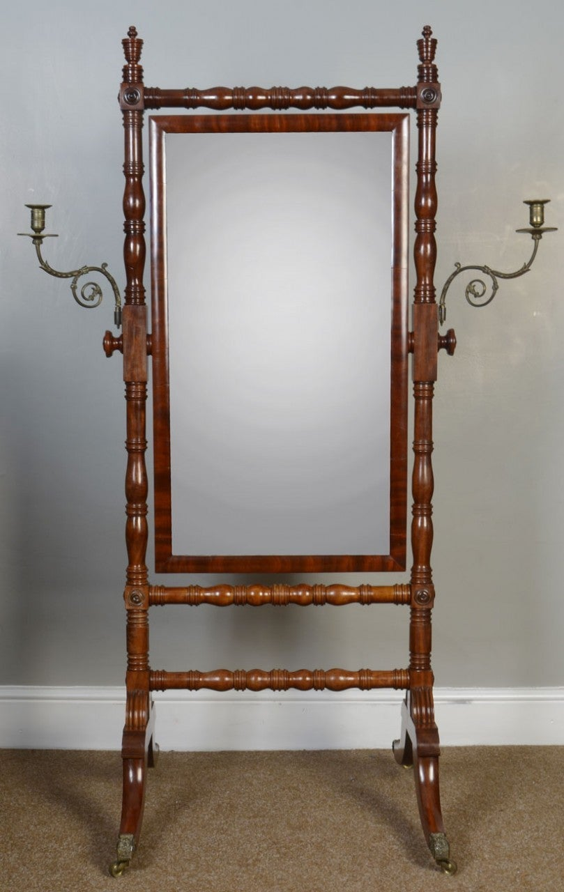 Regency mahogany cheval mirror, the rectangular plate between turned supports having candle branches and twin stretcher, on splayed reeded sabre legs with bras caps and castors.  Dimensions:  Height: 63 inches Width: 28 inches Depth: 29 inches.
