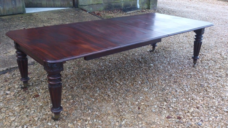 Good solid antique extending dining table. This table is made of very dense grained cuban mahogany which has an interesting grain pattern. The mechanism of the table is so strong that it only needs four legs to support it. That means that none of